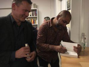 """Buchvernissage von Monika Mansour zu """"Businessplan: Mord"""". Sunil Mann signiert für Christof Gasser. Foto: Bettina Schnerr"""