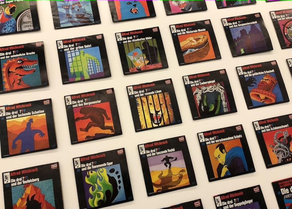 """Buchcover der Serie """"Die drei ???"""" im Eingang zur Ausstellung """"Die drei ??? und das Geheimnis im Turm"""" mit den Illustrationen der Grafikerin Aiga Rasch"""